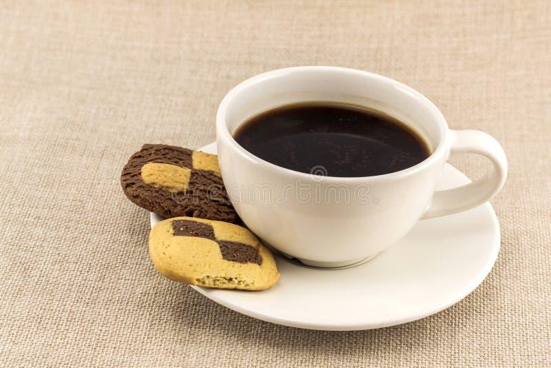 Kop van koffie met koekjesschaak zoals koekjes op jute sackclot royalty-vrije stock foto's
