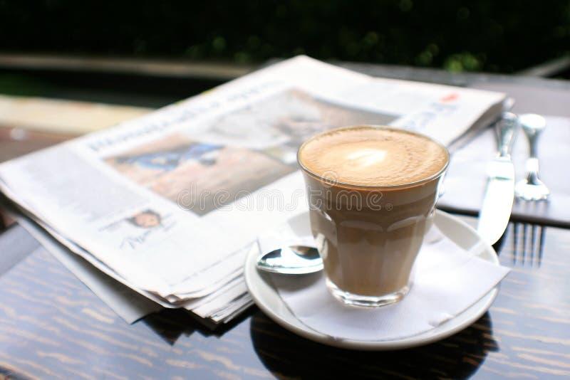 Kop van koffie met nieuwsdocument op lijst stock foto's