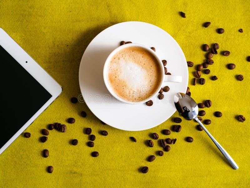 Kop van koffie met tablet op groene achtergrond stock foto's
