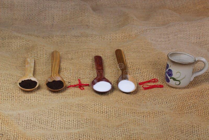 kop van koffie naast houten lepels met koffie en suiker latte cappuccino van de achtergrond de witte hete lijstmelk royalty-vrije stock afbeelding