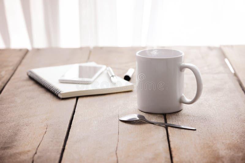 Kop van koffie, notitieboekje, pen en slimme telefoon stock afbeelding