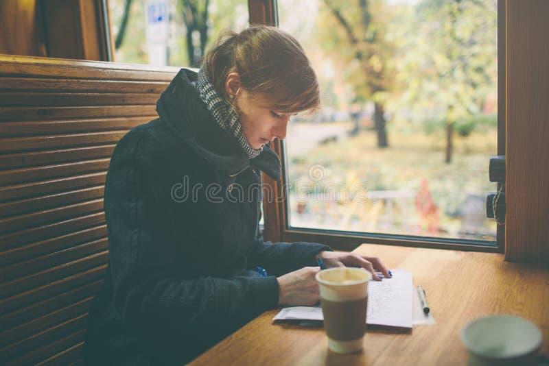 Kop van koffie op de voorgrond met elegante jonge vrouw bij de winkel houten lijst, van de het bedrijfs werkonderbreking mensen,  stock afbeeldingen