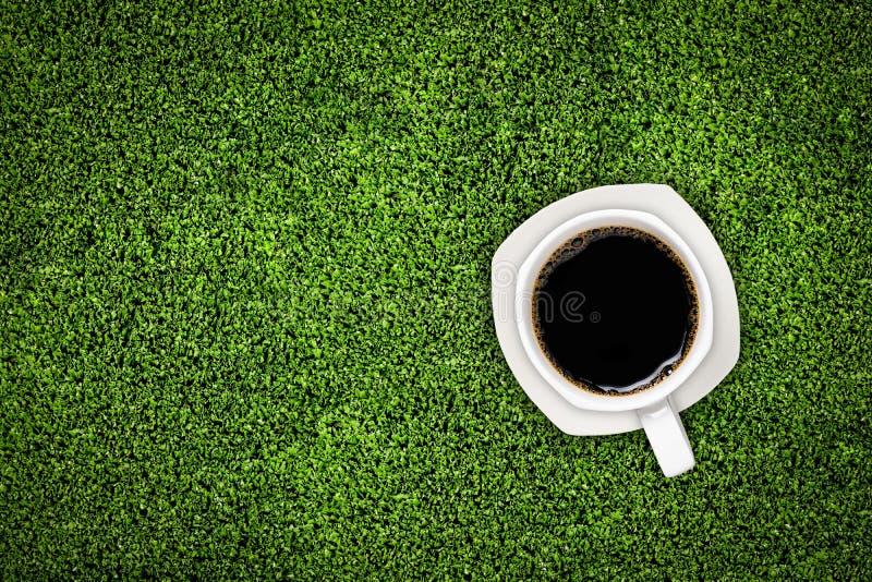 Kop van koffie op groen gras stock afbeeldingen