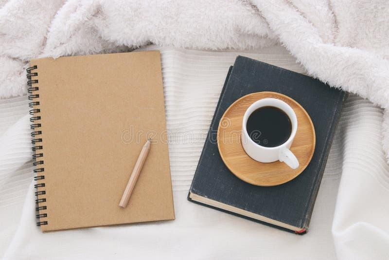 Kop van koffie op het oude boek naast leeg notitieboekje over comfortabele en witte deken Hoogste mening royalty-vrije stock afbeelding