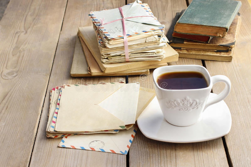 Kop van koffie op houten lijst Uitstekende boeken en stapel van brieven stock afbeelding