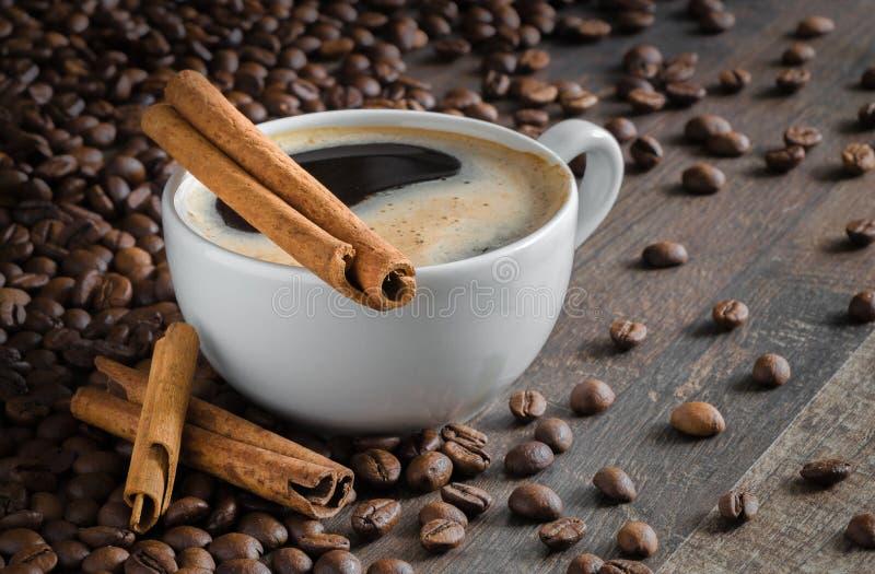 Kop van koffie, pijpjes kaneel, koffiebonen royalty-vrije stock afbeeldingen