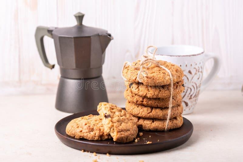 Kop van koffie, stapel havermeelkoekjes, koffiezetapparaat bij de witte houten Eigengemaakte bakkerij als achtergrond royalty-vrije stock foto