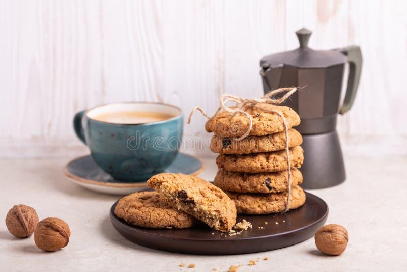 Kop van koffie, stapel havermeelkoekjes, koffiezetapparaat bij de witte houten Eigengemaakte bakkerij als achtergrond stock foto