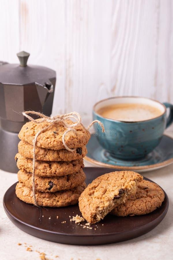 Kop van koffie, stapel havermeelkoekjes, koffiezetapparaat bij de witte houten Eigengemaakte bakkerij als achtergrond royalty-vrije stock fotografie