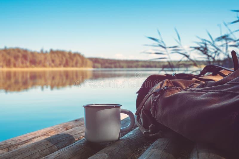 Kop van koffie of thee, rugzak van reiziger op houten pijler op de zomer rustig meer royalty-vrije stock afbeelding