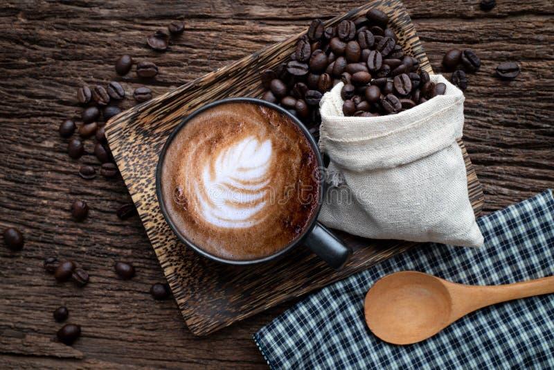 Kop van lattekoffie met koffiebonen op houten lijst stock afbeeldingen