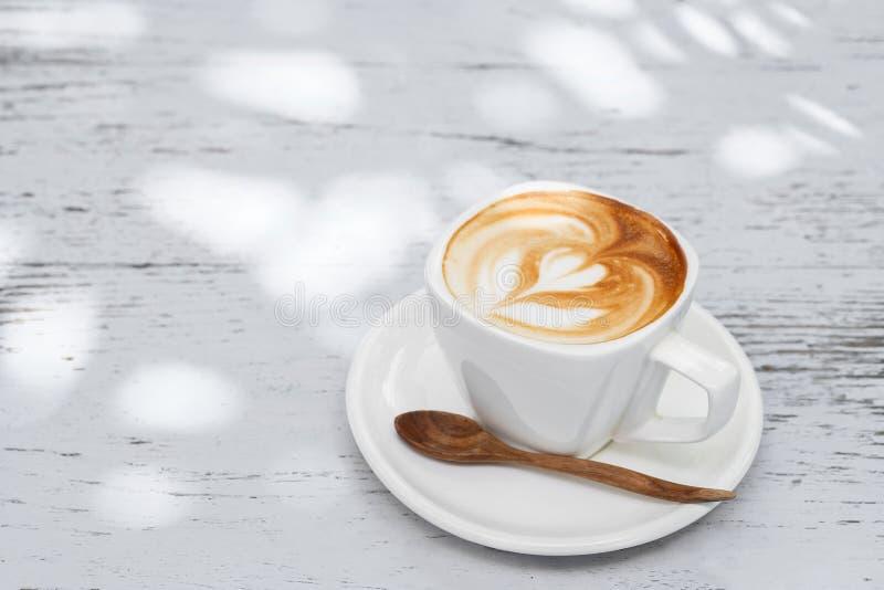 Kop van lattekoffie op witte houten lijst royalty-vrije stock fotografie