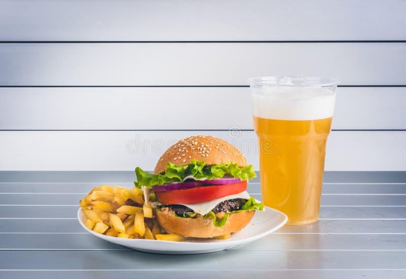 Kop van licht bier met cheeseburger op aluminiumpanelen stock afbeeldingen