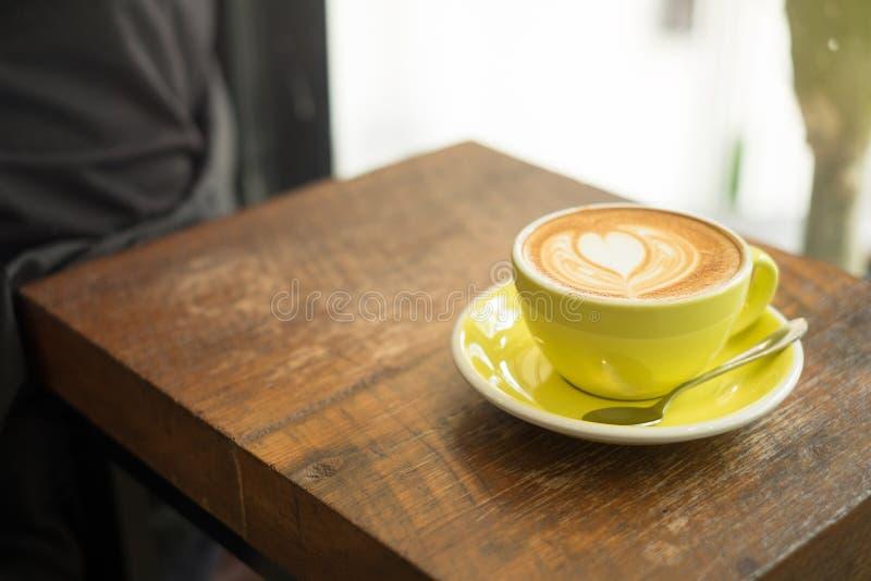 Kop van mooie lattekunst op oude houten achtergrond Hoogste mening stock foto