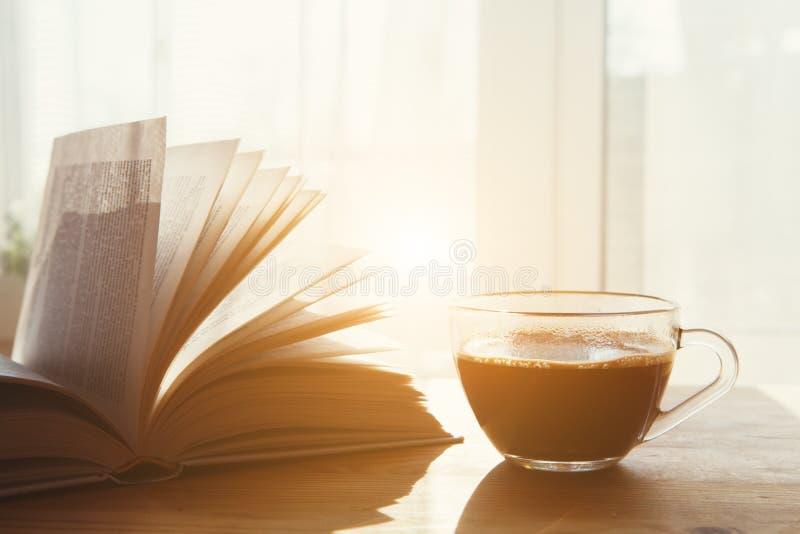 Kop van ochtendkoffie en open boek stock foto's