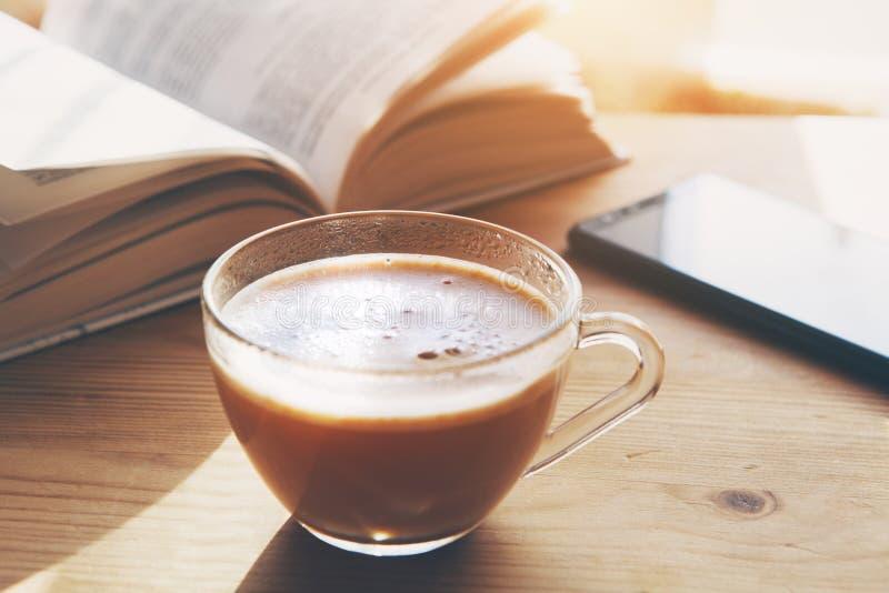 Kop van ochtendkoffie, telefoon en open boek stock afbeelding
