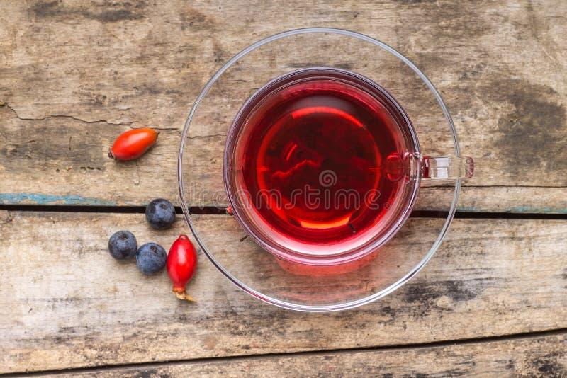 Kop van rode thee met wilde bessen op houten achtergrond royalty-vrije stock foto