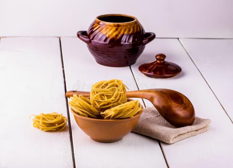 Kop van spaghetti en een houten lepel royalty-vrije stock afbeeldingen