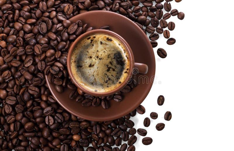Kop van vers gebrouwen die koffie op stapel van koffiebonen op wit worden geïsoleerd stock afbeelding