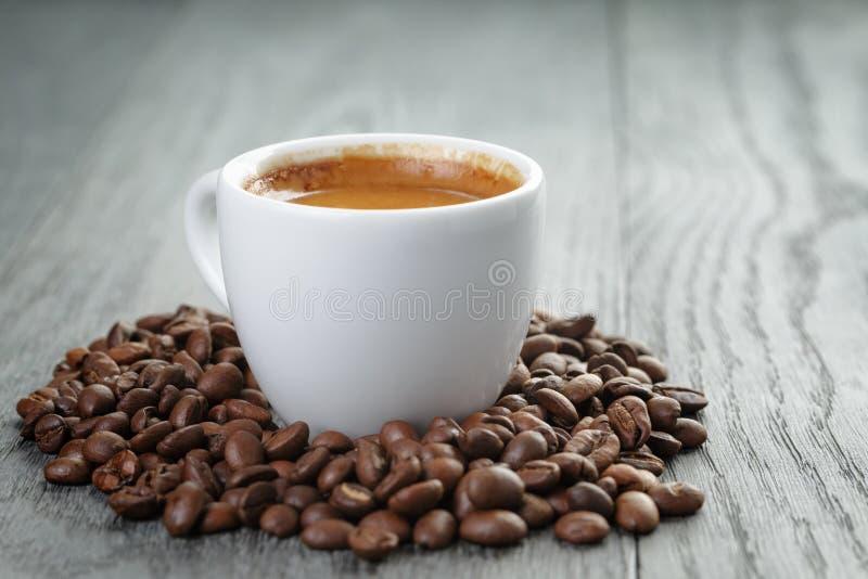 Kop van verse espresso met koffiebonen op eik stock afbeeldingen