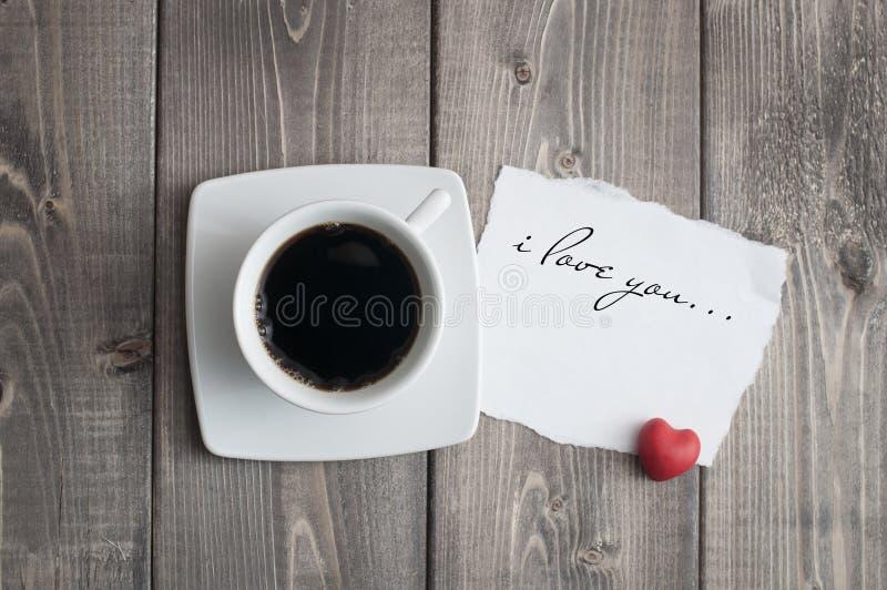Kop van zwart koffie en liefde de dagbericht van Valentine met rode hartvorm royalty-vrije stock fotografie