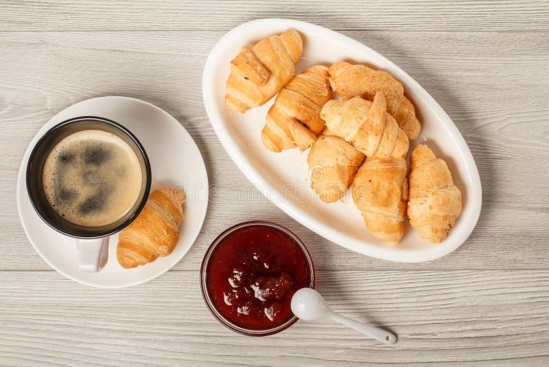 Kop van zwarte koffie met schotel, verse croissants op witte porce stock afbeelding