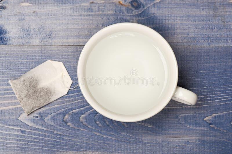 Kop of witte mok met transparante warm water en zak thee Het concept van de theetijd Mok met kokend water en theezakje wordt gevu royalty-vrije stock afbeeldingen