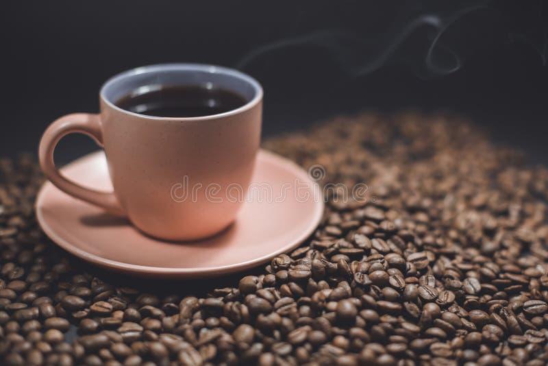 Kop zwarte koffie en geroosterde koffiebonen stock afbeeldingen