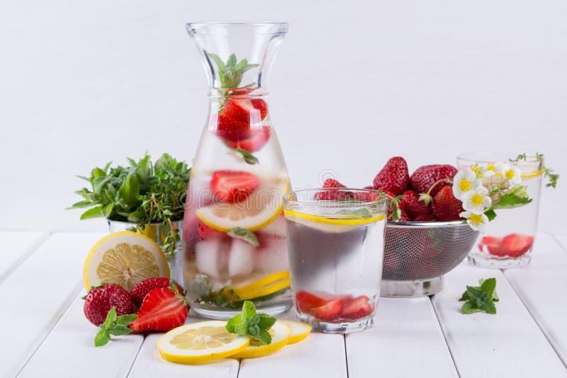Kopalina natchnąca woda z truskawki, lodu, zielarskich i nowych liśćmi na białym tle, domowej roboty detox soda obrazy royalty free