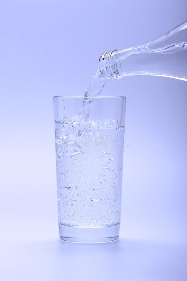 Kopalny świeżej wody dolewanie w szkło od butelki zdjęcia royalty free