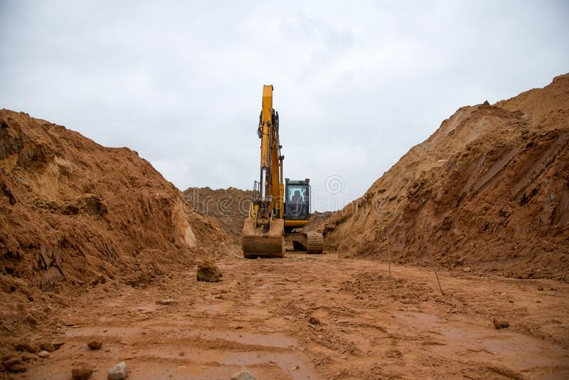 Koparka wykopuje duży rów do układania rur Koparka przy wykonywaniu robót ziemnych na budowie Ciężki sprzęt do przemieszczania zi zdjęcie royalty free