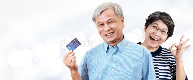 Kopbal van gelukkig Aziatisch vrolijk hoger paar, gepensioneerden of oudere ouders die en creditcard met binnen tevredenheid glim stock fotografie