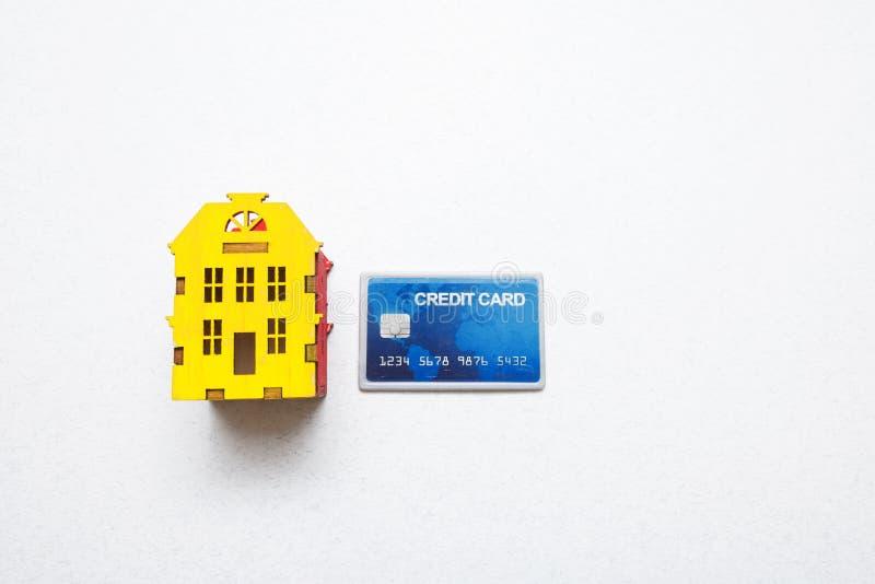 Kopend een huis op krediet, hypotheek miniatuurhuis en creditcard op witte achtergrond met exemplaarruimte stock foto