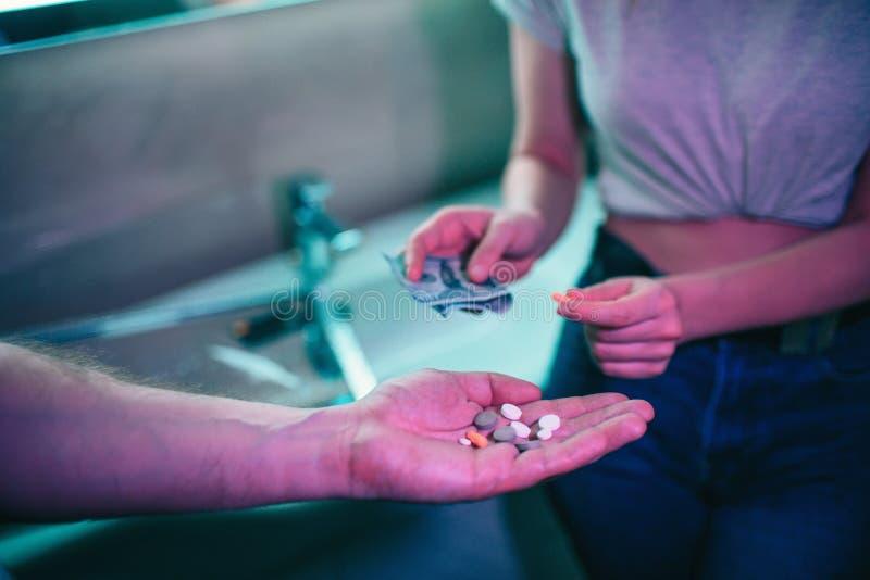 Kopende drugs Drugshandel en verkoop Hand van drugverslaafde met geld het kopen drugs van drugdealer in nachtclub royalty-vrije stock afbeelding
