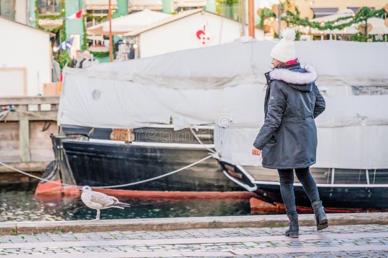 Kopenhagen, Denemarken 27 november, 2018 Jonge vrouw die neer op de meeuw in de Nyhavn-haven kijken stock foto's