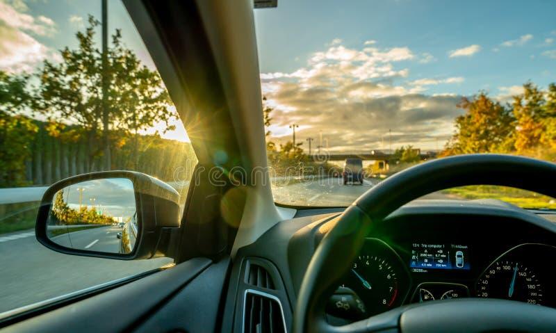 Kopenhagen-Dinamarca 19 de outubro de 2018: Interior do carro ao conduzir em uma estrada no por do sol foto de stock royalty free