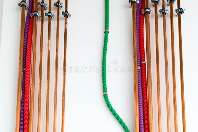 Koperpijpen en kleurrijke plastic buizen voor elektro bedrading op een witte muur royalty-vrije stock afbeelding