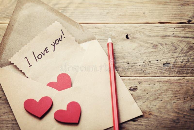 Koperta, list, czerwoni serca lub notatki, kocham ciebie na nieociosanym drewnianym stole dla walentynka dnia w retro tonowaniu obrazy royalty free