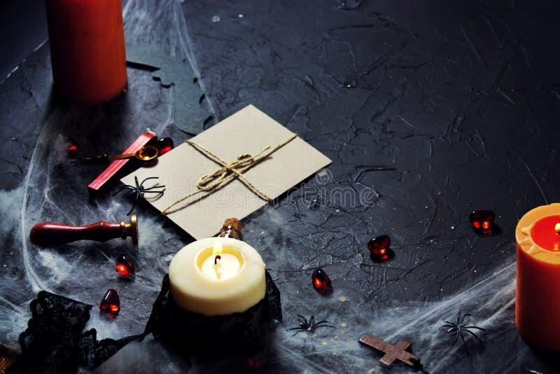 koperta z rocznikiem halloween z pieczÄ™ciÄ…. pÅ'onÄ…ce Å›wiece i pajÄ…ki w sieci obok drewnianego krzyża. poziome zdjęcie stock