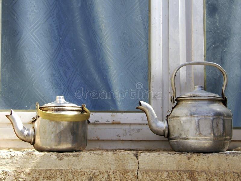 Kopertheepotten die zich aan concrete vensterbank, ketels op het venster van de straatwinkel vóór glas bevinden stock foto