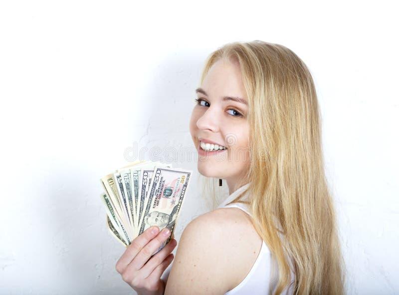 Kopf geschossen von der glücklichen lächelnden Frau, die das Bargeld lokalisiert auf weißer Studiowand übergibt stockfotos