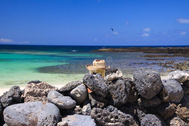 Kopf von Blondinen mit dem Strohhut, der hinter Wand von angehäuften natürlichen Felsen auf Strand mit Türkisozean sitzt lizenzfreie stockbilder