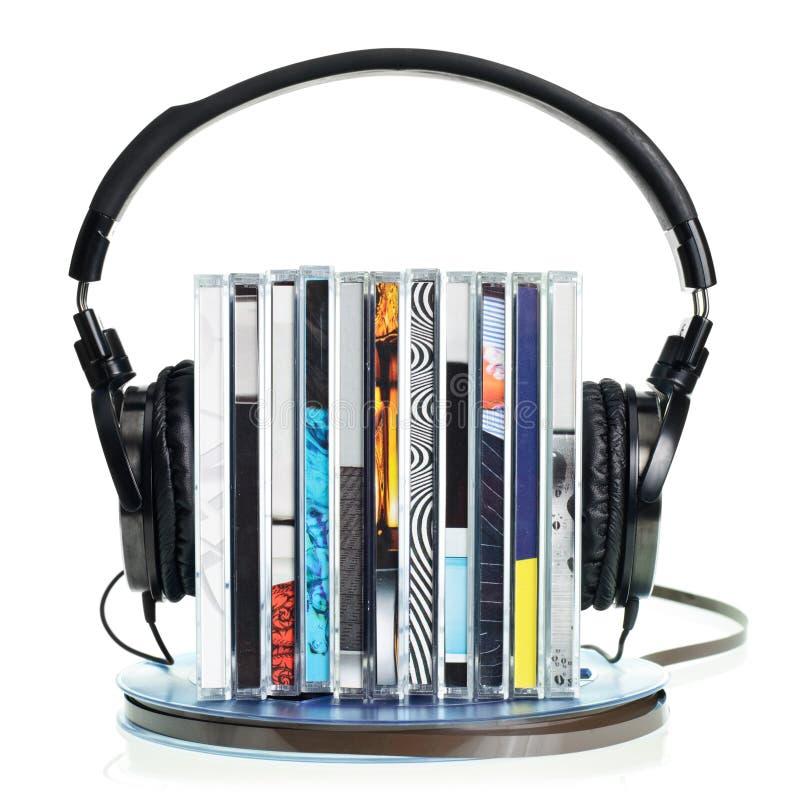 Kopfhörer auf Stapel von Cd und von Bandspuleband stockfotos