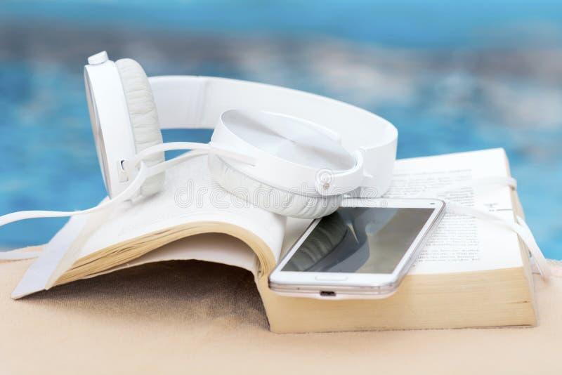 Kopfhörer, Buch und Telefon auf einem Poolhintergrund lizenzfreies stockbild
