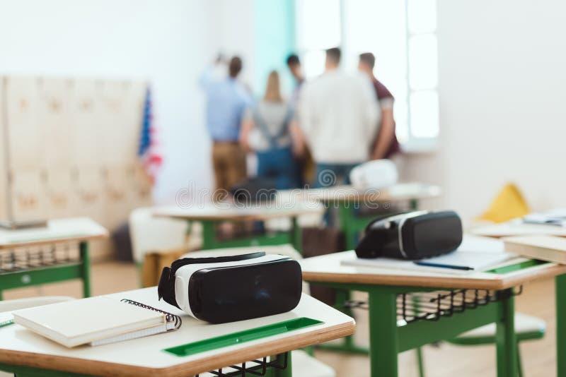 Kopfhörer der virtuellen Realität auf Tabellen mit dem Lehrer und hohen Schülern, die hinten stehen lizenzfreies stockbild