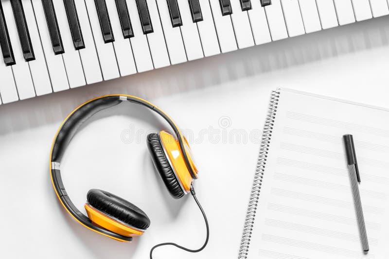 Kopfhörer, Notizbuch und synthesizer im Musikstudio für DJ oder des Schreibtischhintergrundes der Musikerarbeit weißes Draufsicht lizenzfreie stockbilder