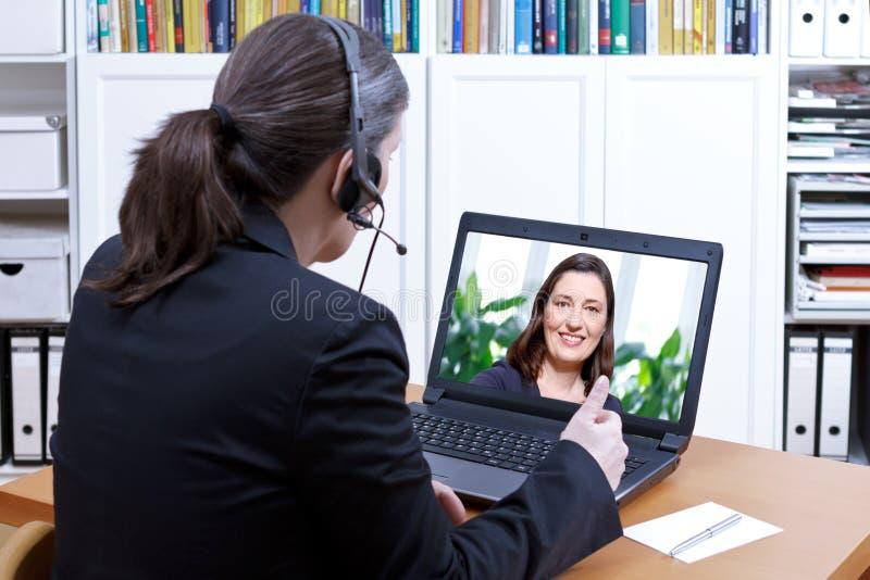 Kopfhöreron-line-Kurs des weiblichen Lehrers stockbild
