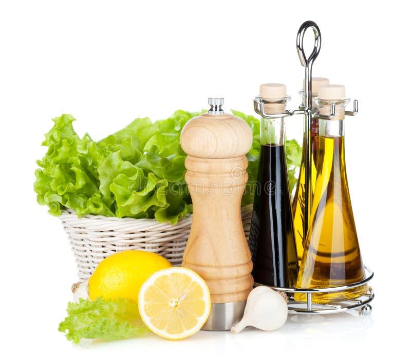 Kopfsalat im Korb mit Zitrone trägt, Pfefferschüttel-apparat Früchte, das Olivenöl lizenzfreie stockfotografie