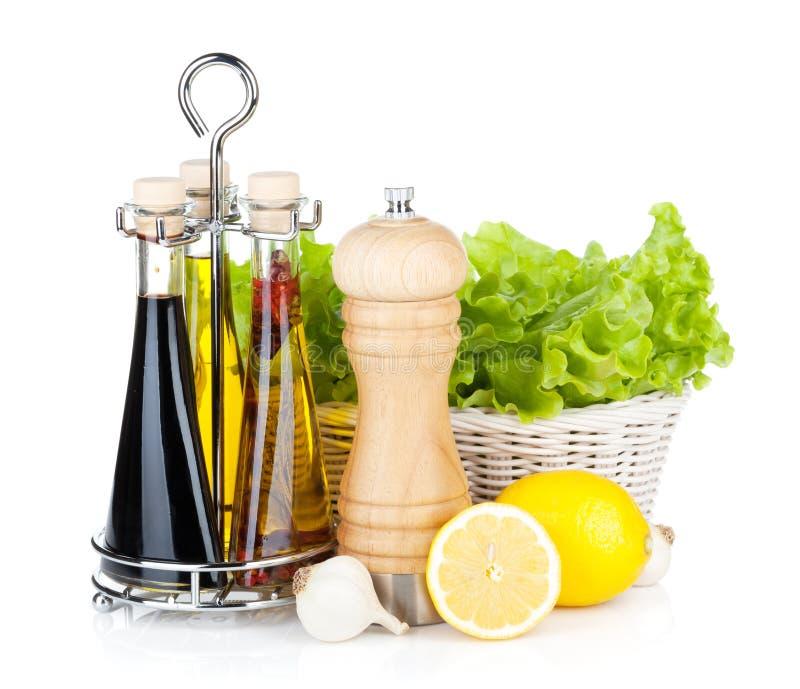 Kopfsalat im Korb mit Zitrone trägt, Pfefferschüttel-apparat Früchte, das Olivenöl lizenzfreie stockbilder