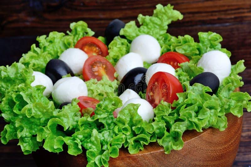 Kopfsalatsalat mit Mozzarellatomate und -olive in einer Schüssel stockfoto